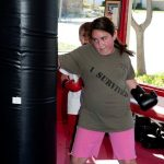 Ruby hits the heavy bag in kickboxing class